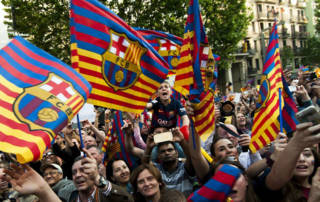 BARCELONA, SPAIN - May 15: Fans welcome FC Barcelona's players as they hold flags and take photos during FC Barcelona's victory parade after winning the Spanish La Liga in Barcelona, Spain on May 15, 2015. (Photo by Albert Llop/Anadolu Agency/Getty Images)