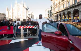Carl Lewis arriva in Piazza Duomo sulla Alfa Romeo Giulia Quadrifoglio che si è aggiudicata il record di categoria sul leggendario circuito di Nurburgring con il tempo di 7'32